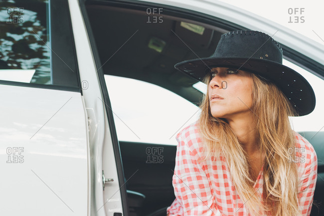 Attractive Woman In Cowgirl Hat Sitting In The Door Of A White Car