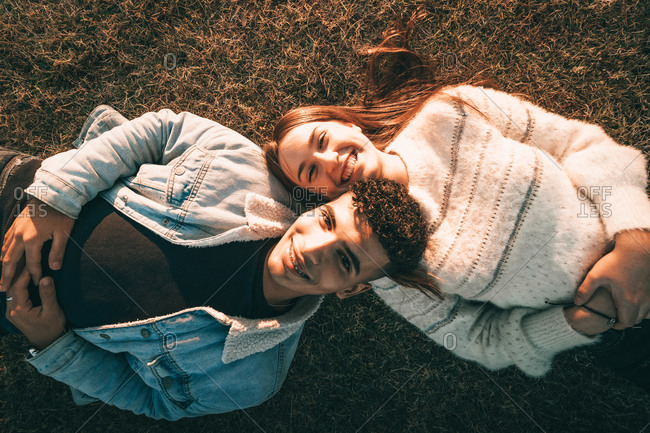 Aerial Shot Of A Smiling Couple Lying On The Grass