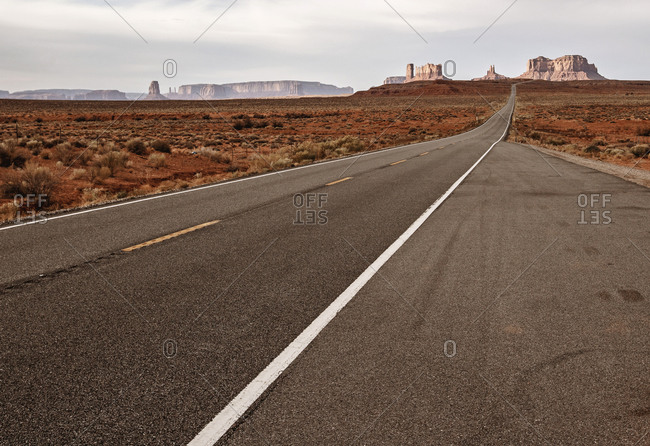 lonely dramatic landscape with road running to Monument Valley, Utah