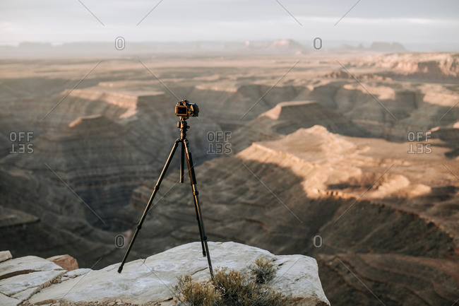 camera and tripod on cliff edge in front of scenic view, Utah desert
