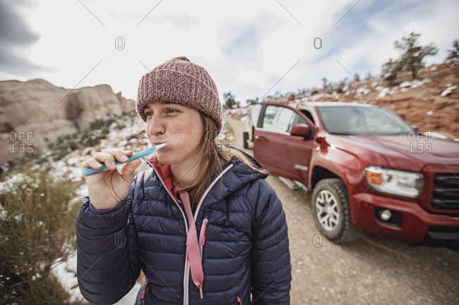 Woman in jacket and hat brushes teeth while car camping in Utah desert