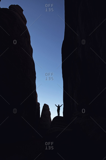 hiker stands silhouetted in deep Canyon with blue sky, Moab Utah