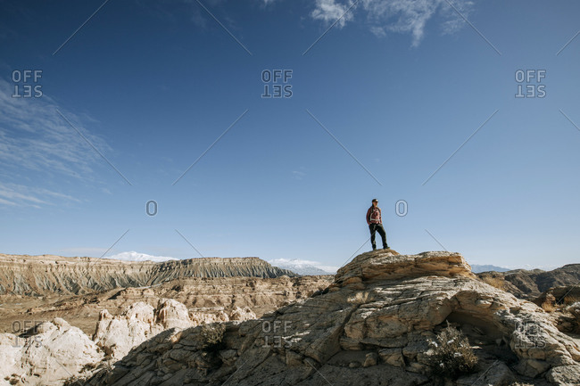 Female hiker looks at view from summit Capital Reef National Park