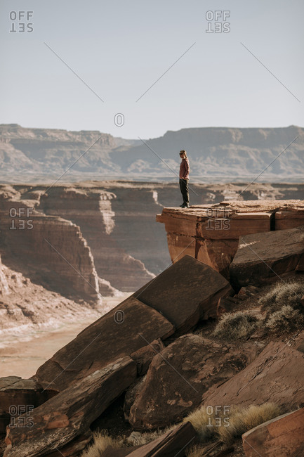 woman stand on edge of high cliff looking over desert, Hite, Utah