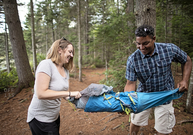 African American man and caucasian woman prepare to set up tent