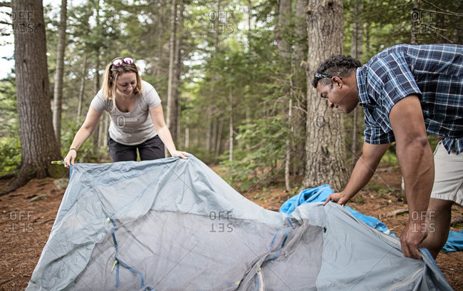 Multi racial couple set up tent in woods on Appalachian Trail, Maine