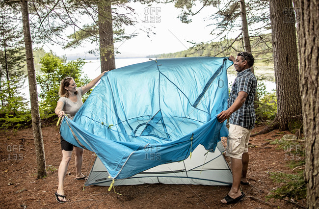 Couple set up blue tent near lake while camping in woods in Maine