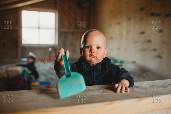 Little boy at indoor playground with shovel playing with sand winter
