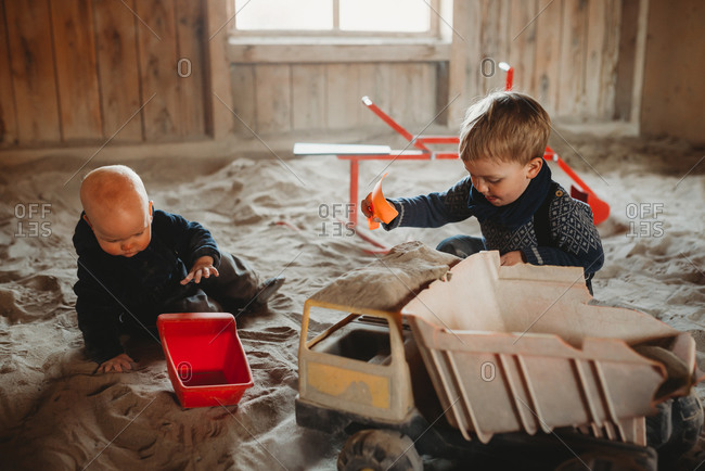 Brothers playing with trucks and shovels in outdoor sandbox in winter