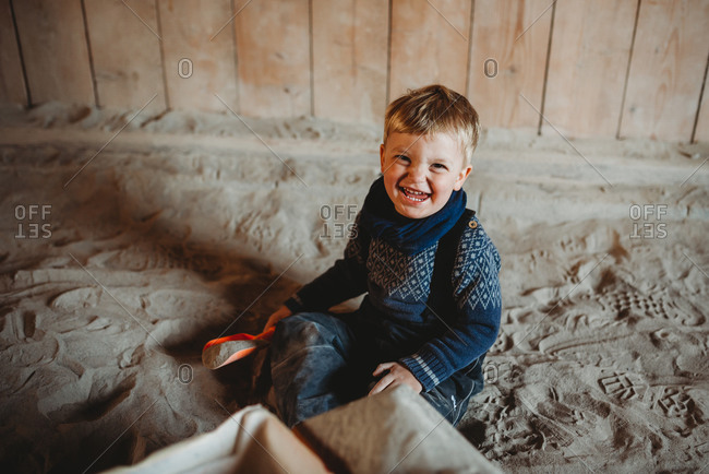 Little boy smiling playing in sand in winter with shovel in hand