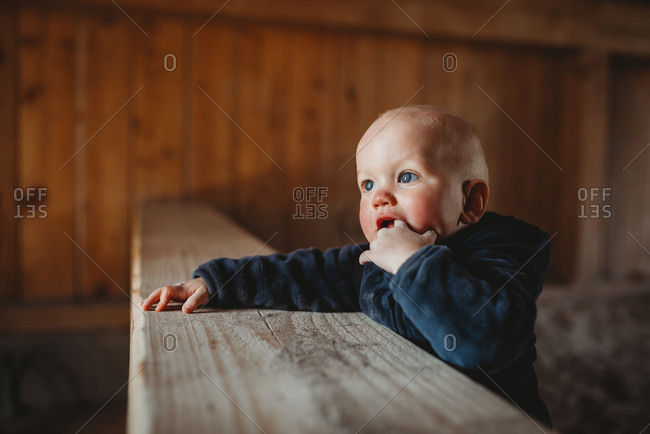 Baby boy with blue eyes putting finger in mouth teething outside