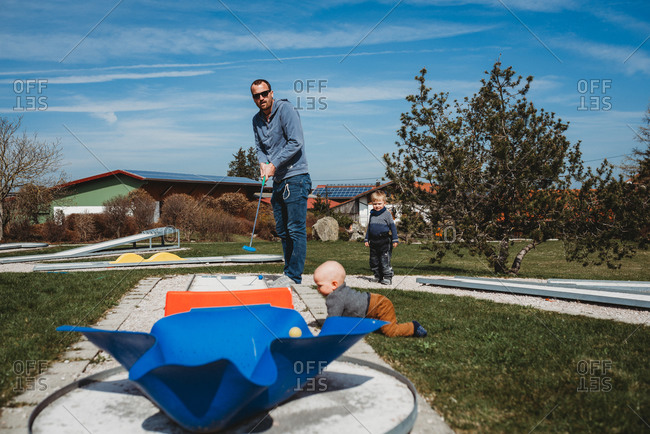 Father and son playing mini golf in farm on sunny day