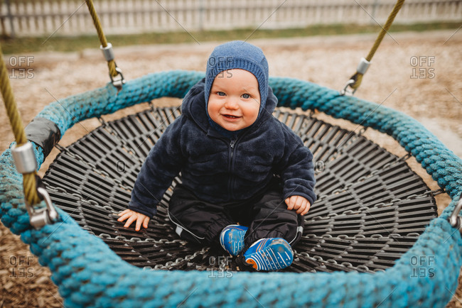Baby boy wearing blue in playground nest hammock smiling in winter