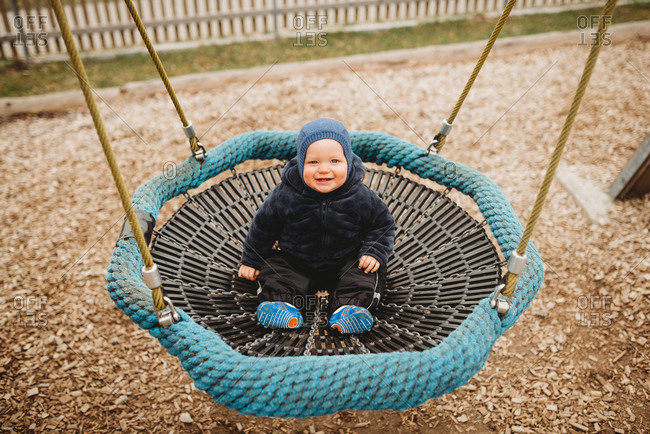 Cute baby in outdoor playground in winter on a nest hammock