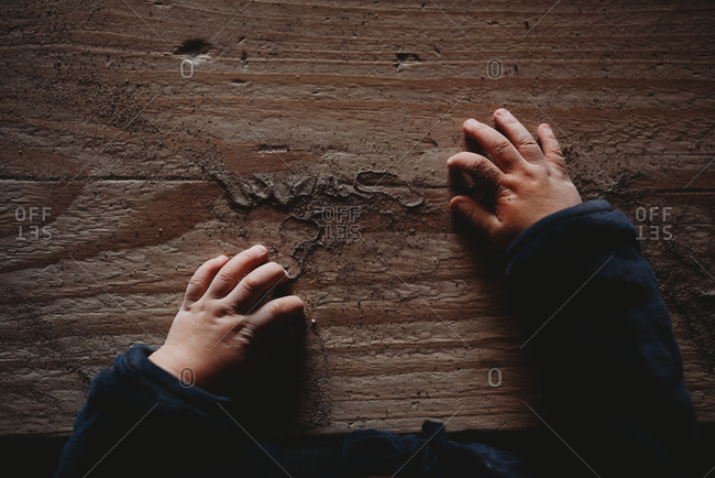 Dimpled baby hands on wooden board full of sand