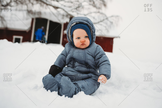 Adorable baby sitting on snow touching snow for first time at the farm