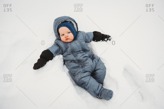 Adorable Baby looking sad lying on snow wearing a snowsuit t