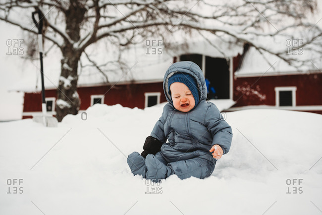 Baby crying sitting on snow in Norway with red barn behind