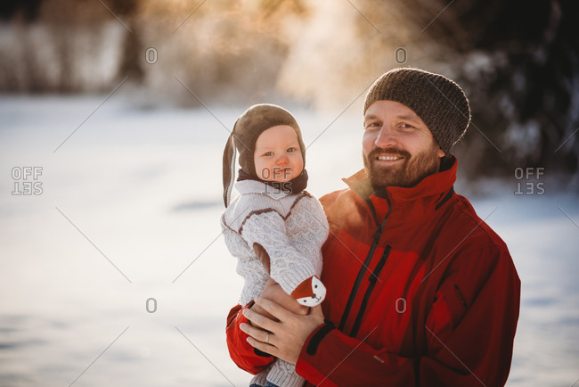 Cute baby boy and his dad smiling in Norway snowy woods in sunset