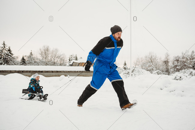 Fun dad pulling sleigh where son is sitting on in winter snowy woods