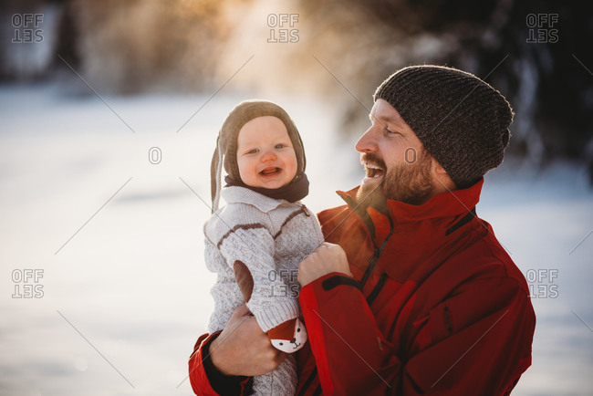 Father holding beautiful smiling baby outside in snow in Scandinavia
