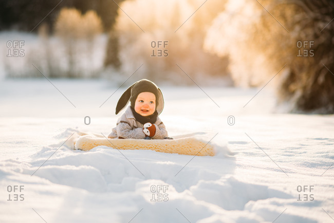 Cute baby smiling sitting on snow during sunset in Norwegian forest