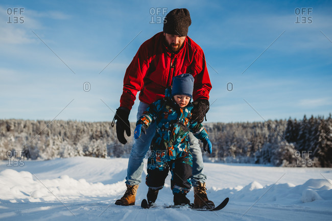 Father teaching son to cross country ski in winter wonderland Norway