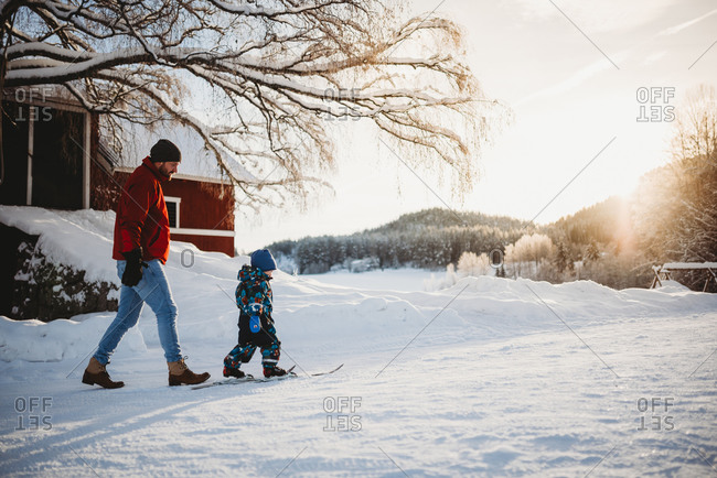 Father teaching son to cross country ski in winter in farm in Norway