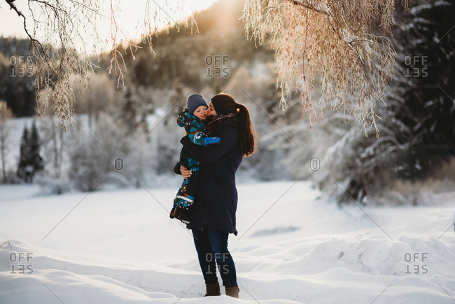 Mother kissing son in mountains full of snow on sunny winter day