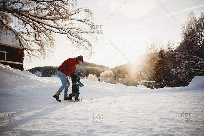 Dad teaching son to cross country ski in farm winter wonderland Norway