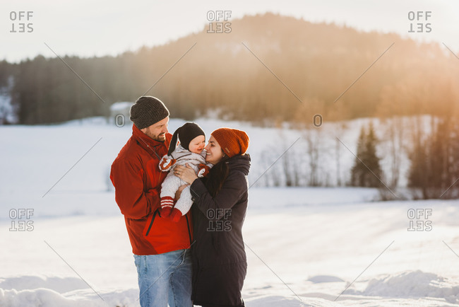 Cute baby and parents in snowy mountains in winter sunny day smiling