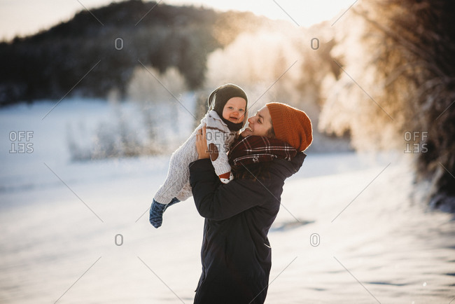 Beautiful baby and mother smiling on sunny day in mountains in winter