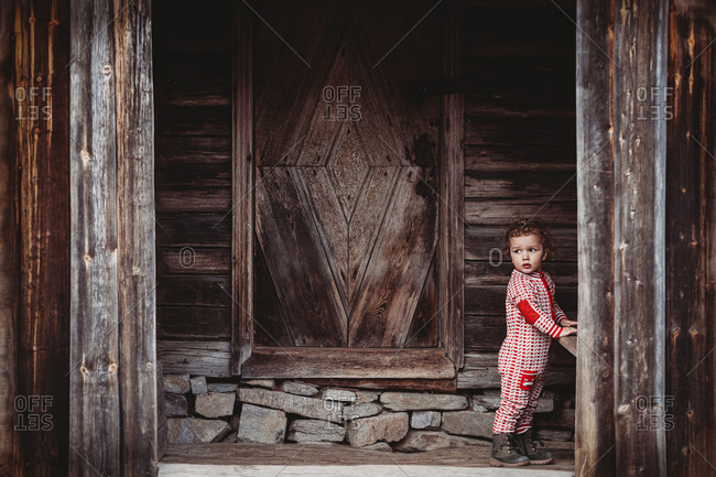Boy wearing wool onesie in front porch of old wooden house in Norway