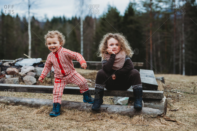 Brother and sister sitting on wooden log outside in forest in winter