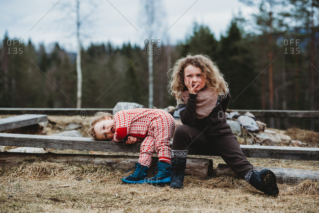 Boy and girl sitting on wooden log bored in the forest in winter