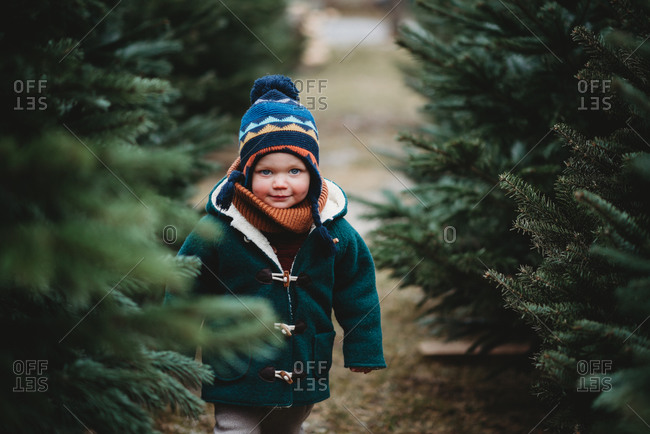 Adorable child wearing wool coat walking between Christmas trees