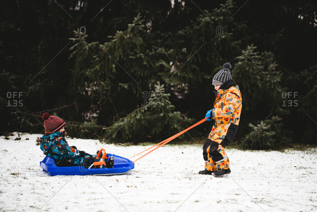 Child pulling sleigh with brother sitting on it in their backyard