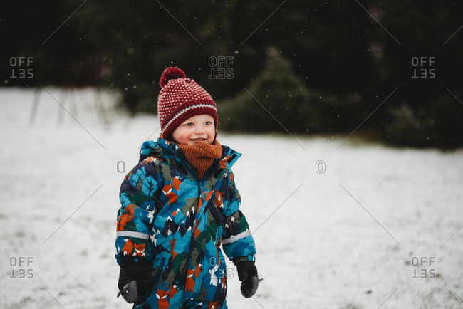 Beautiful boy smiling outside in park on cold snowy day in winter