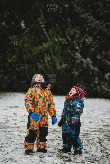 Fun children sticking tongue out to taste snowflakes on cold snowy day