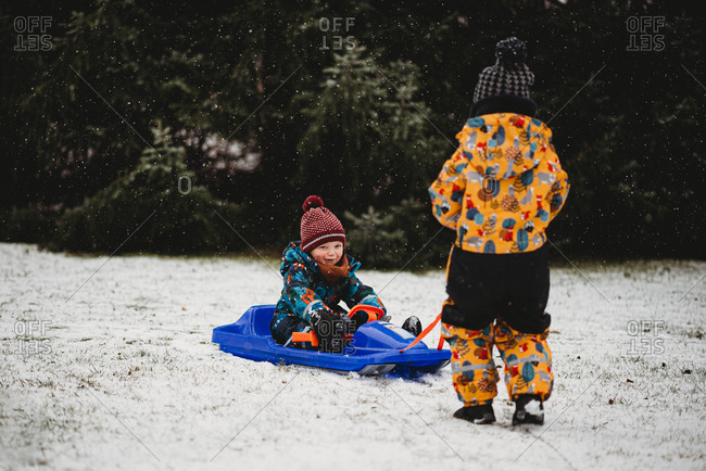 Little boy smiling sitting on sleigh on cold snowy day in Germany