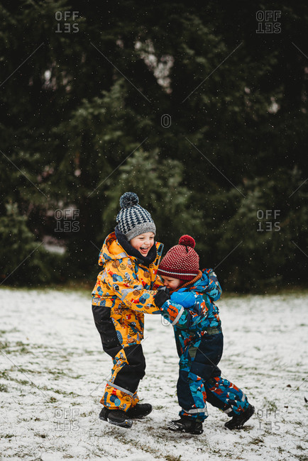 Kids having fun outside at park playing in snow on winter day Europe