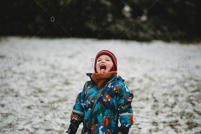 Adorable child sticking his tongue out tasting snowflakes in winter