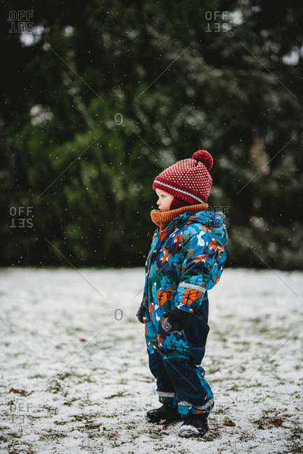 Profile of adorable young child standing at park on snowy day in winter