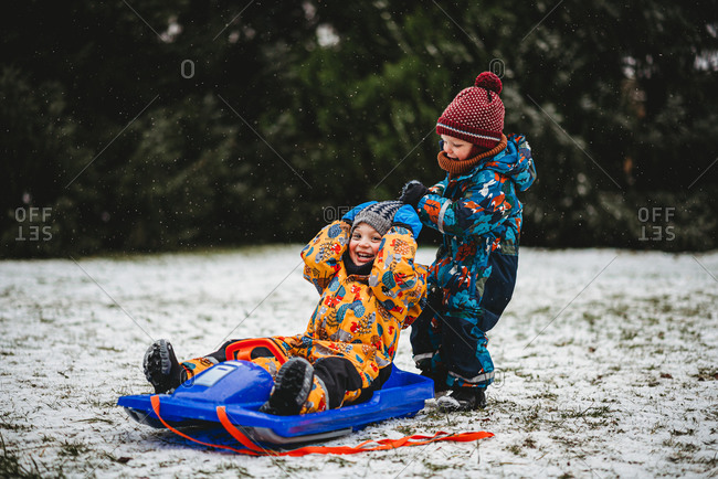 Young kids playing with sleigh in snow at park with snowsuits and hats