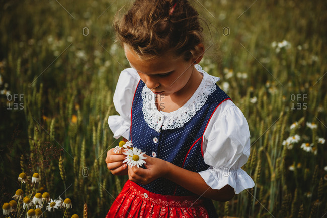 Beautiful girl collecting flowers in the field wearing a German Dirndl