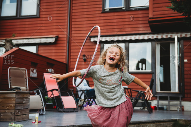 Cute girl having fun with hula hoop in backyard with red wooden house