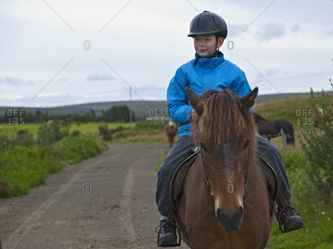 teenage boy riding Icelandic horse in remote location
