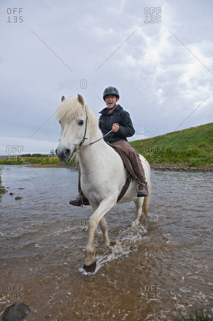 teenage boy riding Icelandic horse in remote location