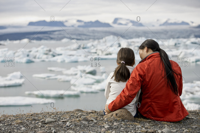 Mother and daughter looking at glacier lagoon in Iceland
