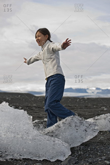 girl balancing on stranded iceberg at glacier lagoon in Iceland